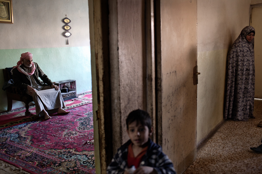 Iraqi widow and mother of three Adwiya Jubar Gatie stands in her home in Baghdad, Iraq. Gatie's husband was killed during sectarian violence while working as a taxi driver in Baghdad.