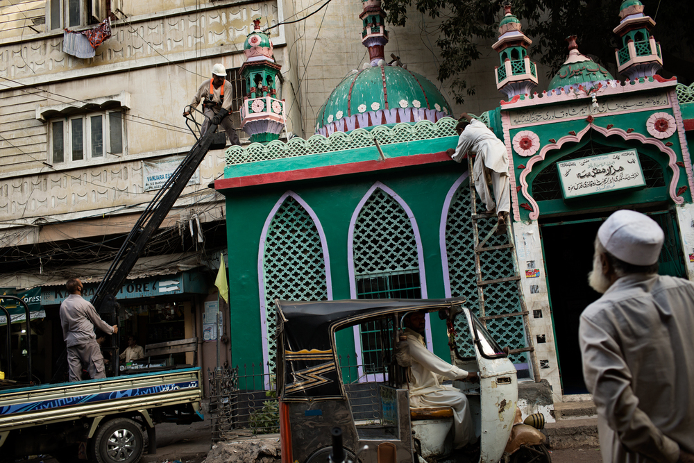 A maintenance team from the Karachi Electricity Supply Company remove illegal power lines from a mosque in Lyari Town, Karachi, Pakistan.