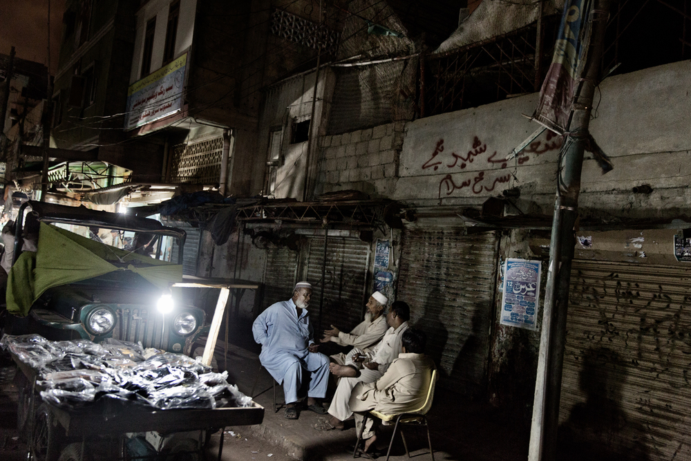 Pakistani men interact on the street with lights powered by motorcycle batteries during load-shedding in Lyari Town, Karachi, Pakistan.