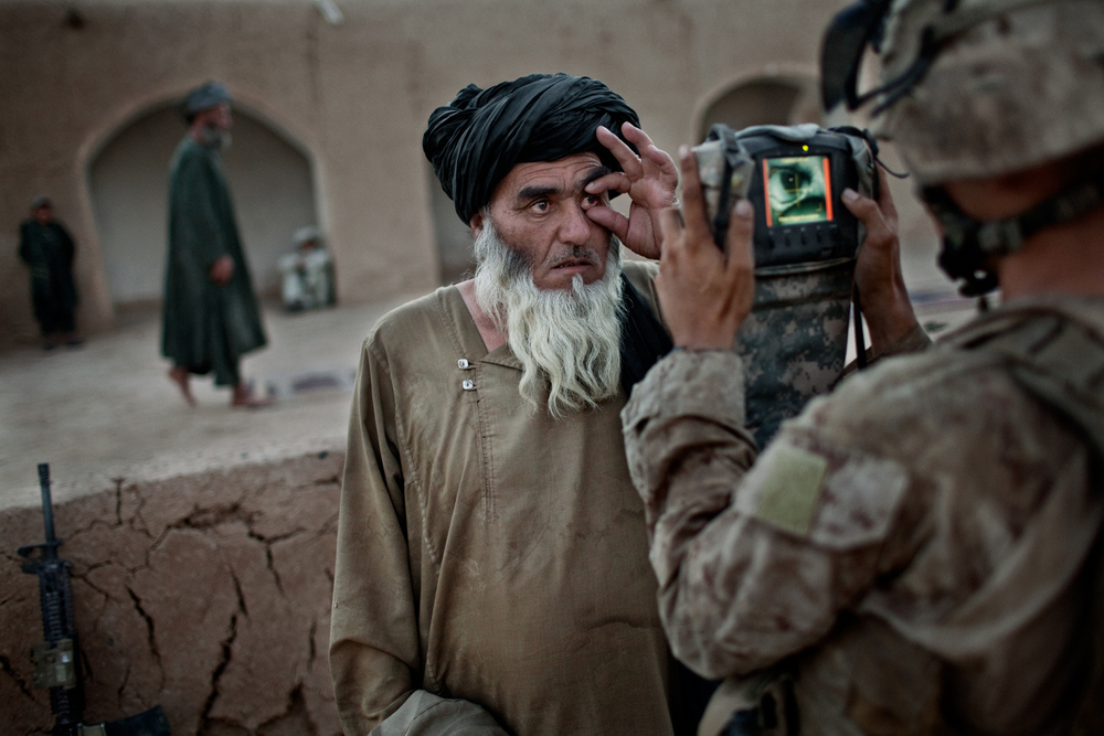 A U.S. Marine records the biometric data of an Afghan villager at a mosque in Marja District, Helmand Province, Afghanistan.