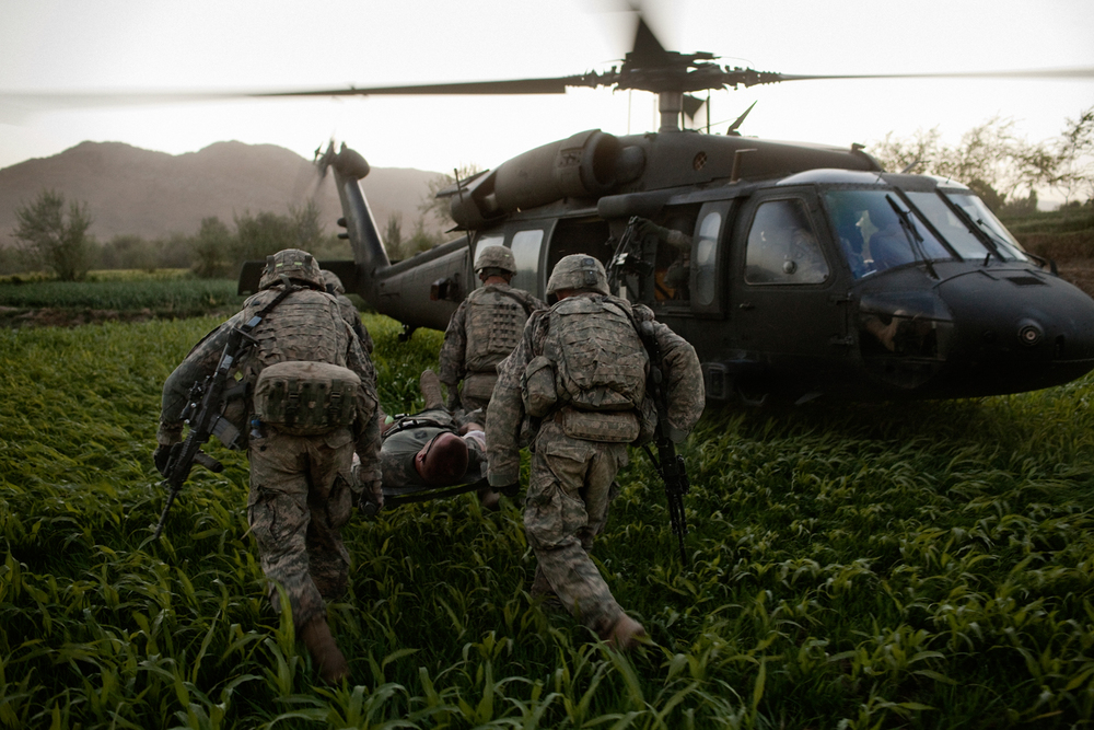 Sergeant Chet Millard is carried on a stretcher to a medical evacuation helicopter after he was injured in an improvised explosive device attack on his vehicle in the Tangi Valley, Wardak Province, Afghanistan.