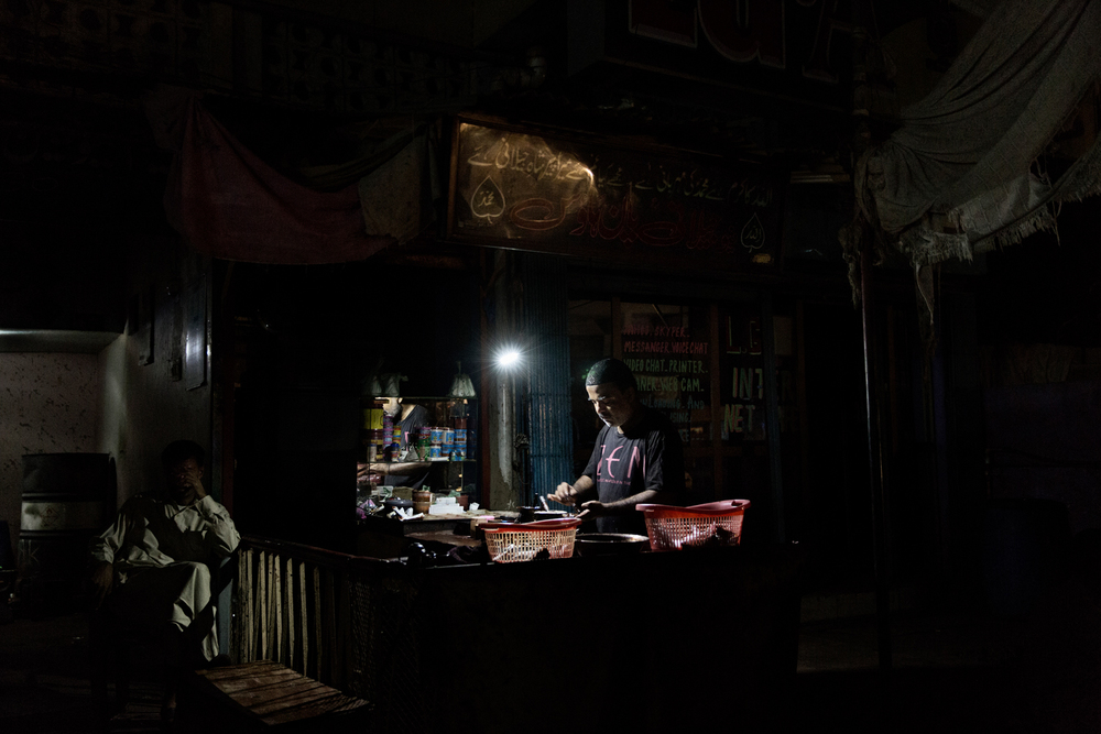 A Paan seller works under a battery torch during load shedding in Lyari Town, Karachi, Pakistan.