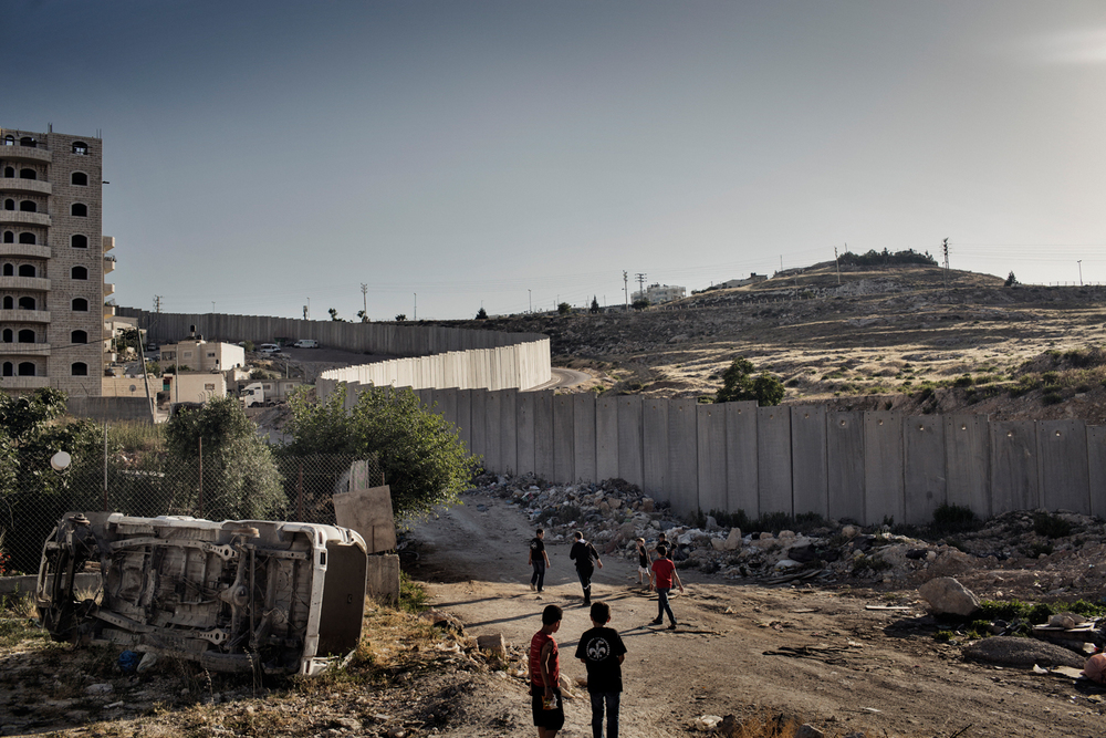 Children walk past the separation barrier surrounding Shuafat refugee camp, a dividing wall separating the camp from East Jerusalem, Israel.