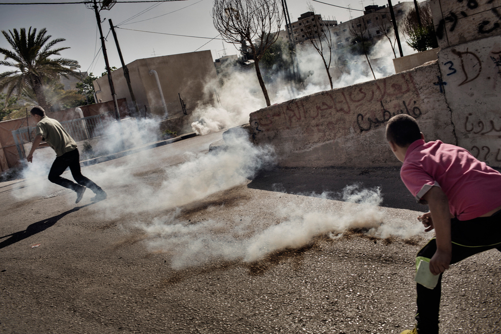 Palestinian children throw tear gas canisters fired at them by Israeli military in response to rock throwing at Aida refugee camp in Bethlehem, West Bank, Palestinian Territories.