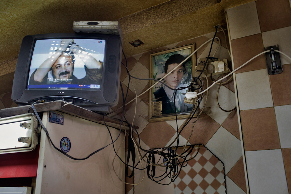 A television in a restaurant shows imprisoned Palestinian activist Marwan Barghouti next to a portrait of a martyr hung on a wall in Shuafat refugee camp, Jerusalem, Israel.