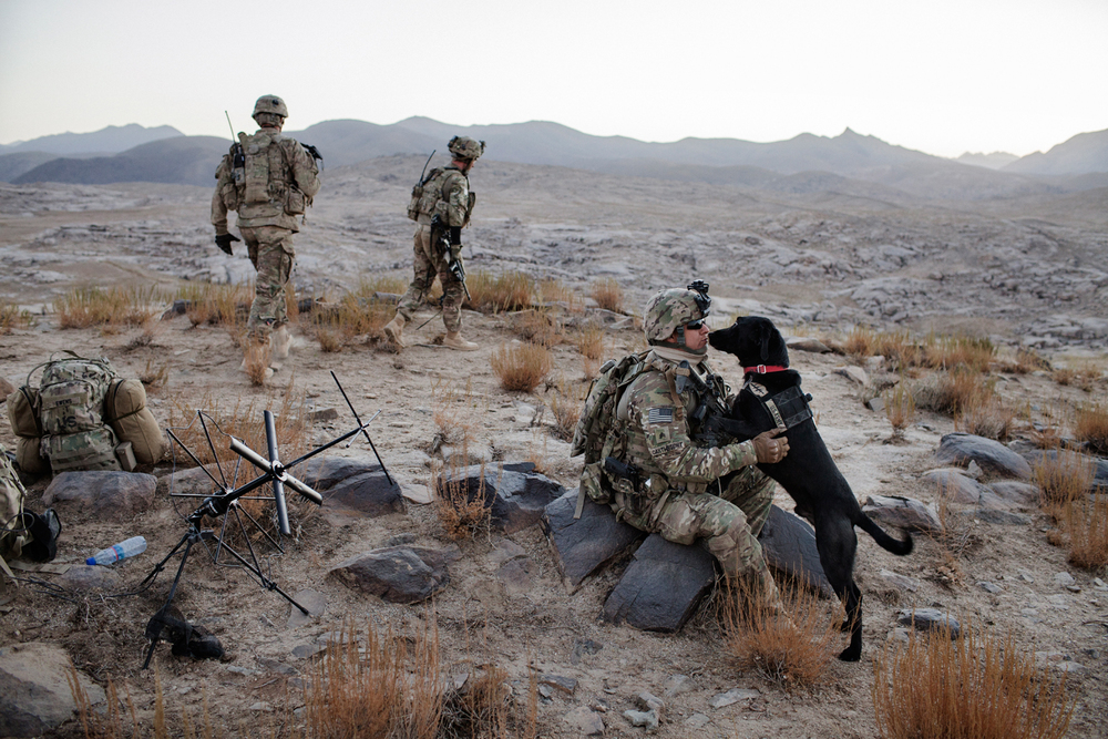 Military Working Dog handler Sergeant Jason Cartwright sits with specialised search dog Isaac, a Black Labrador explosives dog, during an operation in May Neshin, Kandahar, Afghanistan.