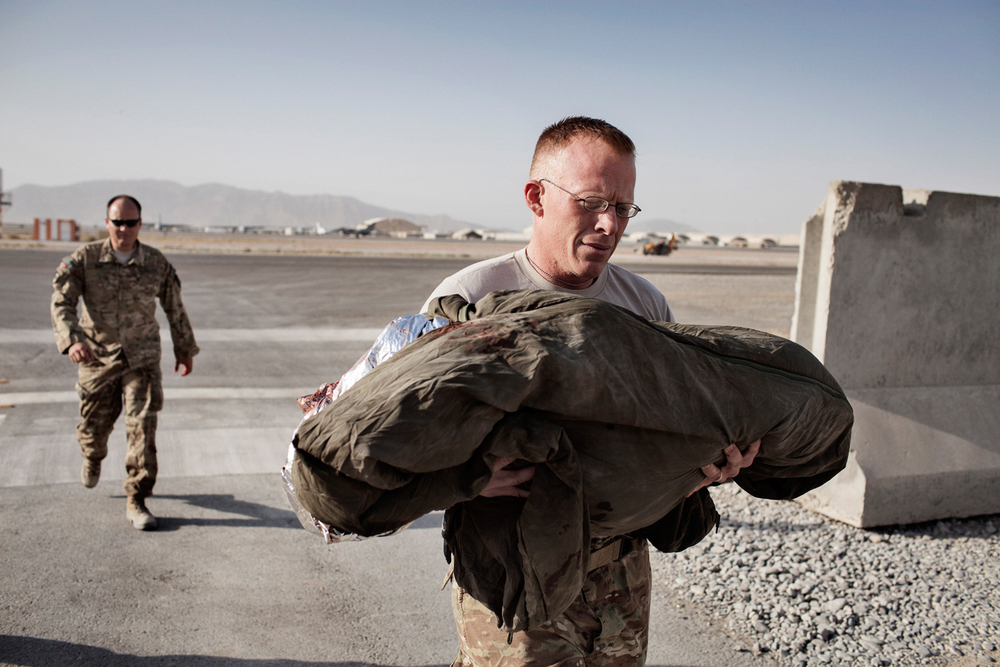 Sergeant Thomas Sager, a U.S. Army Veterinary Technician from the 438th Medical Detachment Role 3 Veterinary Medical Surgical Team, carries a fallen Military Working Dog Dinomt, a German Shepherd explosives patrol dog, from a medical evacuation helicopter at Kandahar Airfield, Afghanistan.