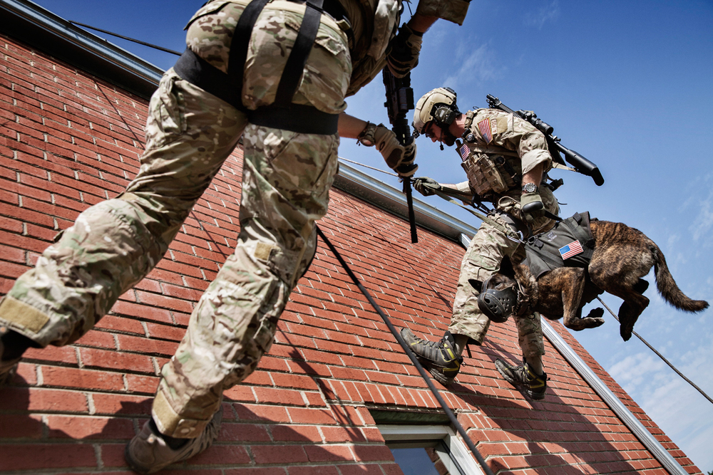 Jason Crafter, K2 Trainer and Instructor (L) and Fred Fusco, K2 Trainer and Instructor perform a demonstration of repelling down a roof with a Military Working Dog at a K2 facility in Ellerbe, North Carolina, U.S.A.