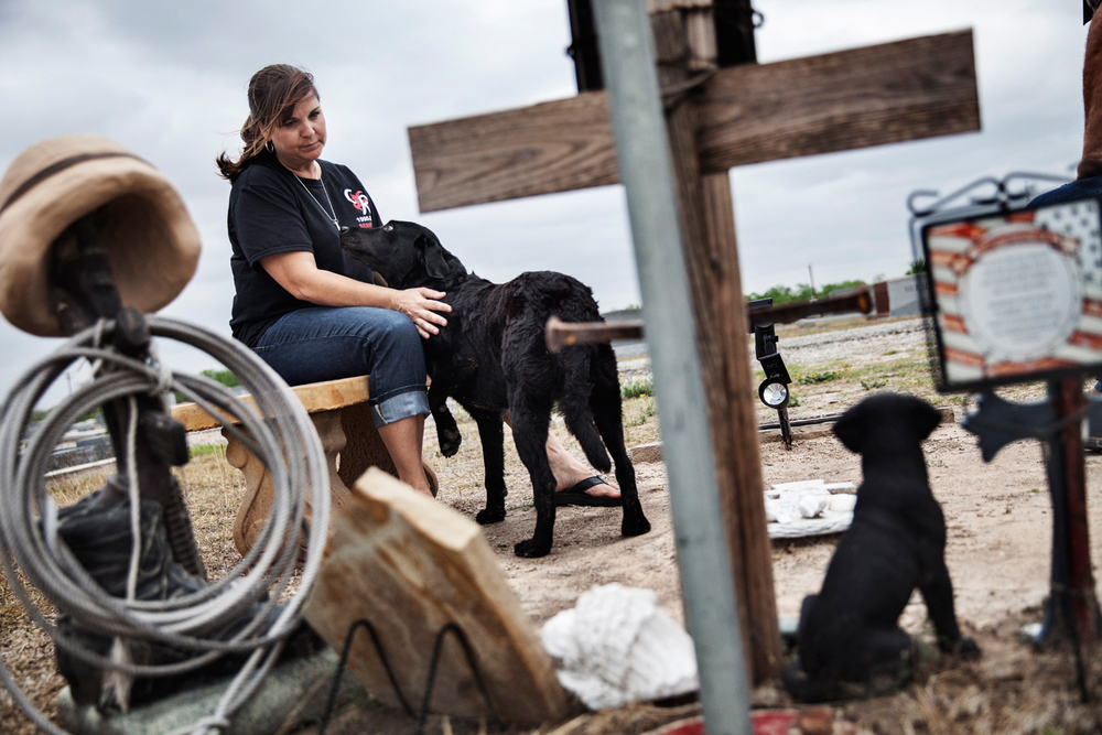 Kathy Rusk sits at the grave of her son, Private First Class Colton Rusk, with her sons Improvised Detection Dog Eli, at Sons Hermann Cemetery, Orange Grove, Texas, U.S.A.