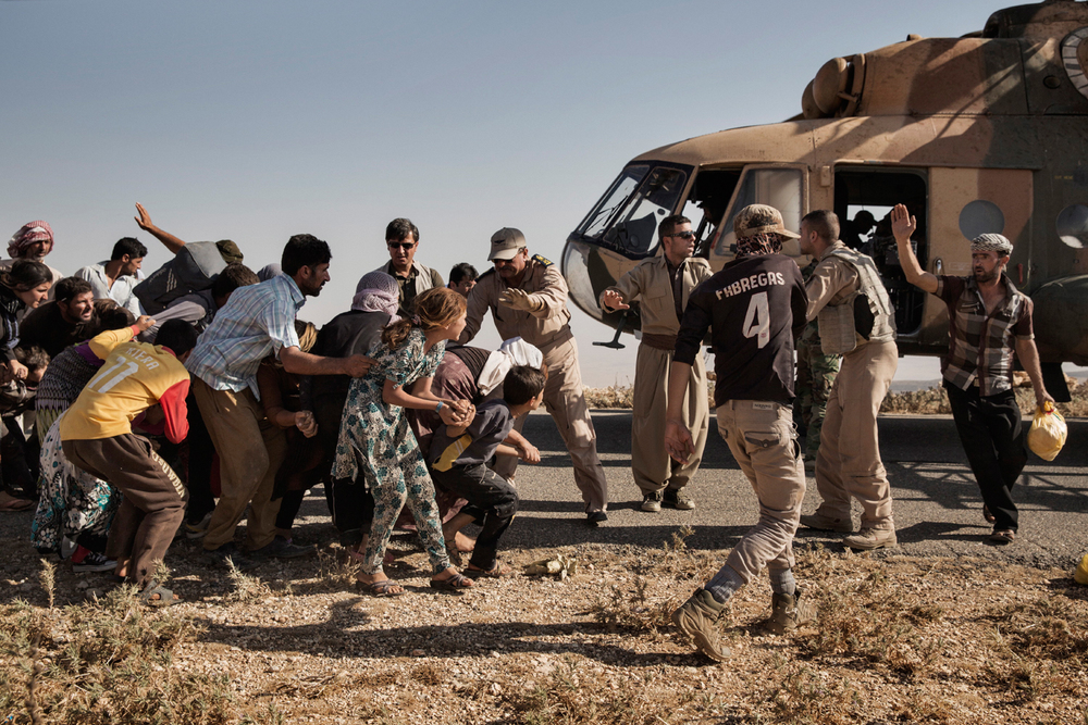 An Iraqi Military flight organized by Kurdish peshmerga forces delivers aid to trapped Yazidis in the mountains of Sinjar, Nineveh Province, Iraq on Aug. 12, 2014. After delivering aid and picking up a number of displaced Yazidis, the helicopter crashed while taking off, wounding many and killing the pilot. Photo by Adam Ferguson for The New York Times