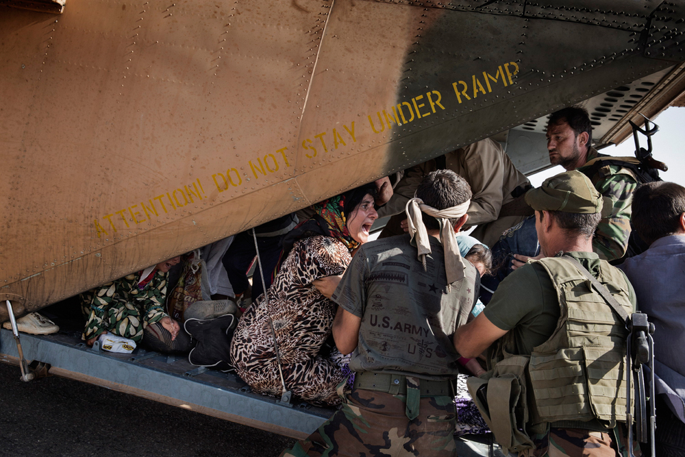 Displaced Yazidis seeking to flee the mountains of Sinjar are removed from an Iraqi Military helicopter after the pilot attempted to lift off and realised the aircraft was overloaded, in Sinjar, Nineveh Province, Iraq on Aug. 12, 2014. The helicopter After delivery aid and picking up a number of IDPs, the helicopter crashed wounding many and killing the pilot. Photo by Adam Ferguson for The New York Times