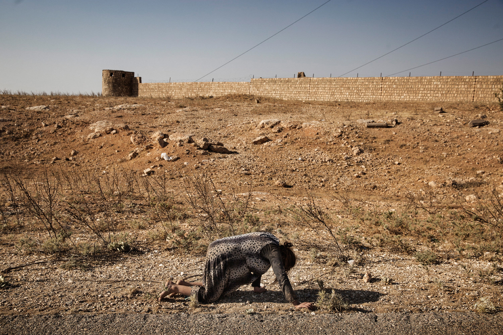 A displaced Yazidi woman crawls on the ground after the Iraqi Military helicopter she was travelling in crashed in the mountains of Sinjar, Nineveh Province, Iraq on Aug. 12, 2014. After delivery aid and picking up a number of IDPs, the helicopter crashed wounding many and killing the pilot. Photo by Adam Ferguson for The New York Times