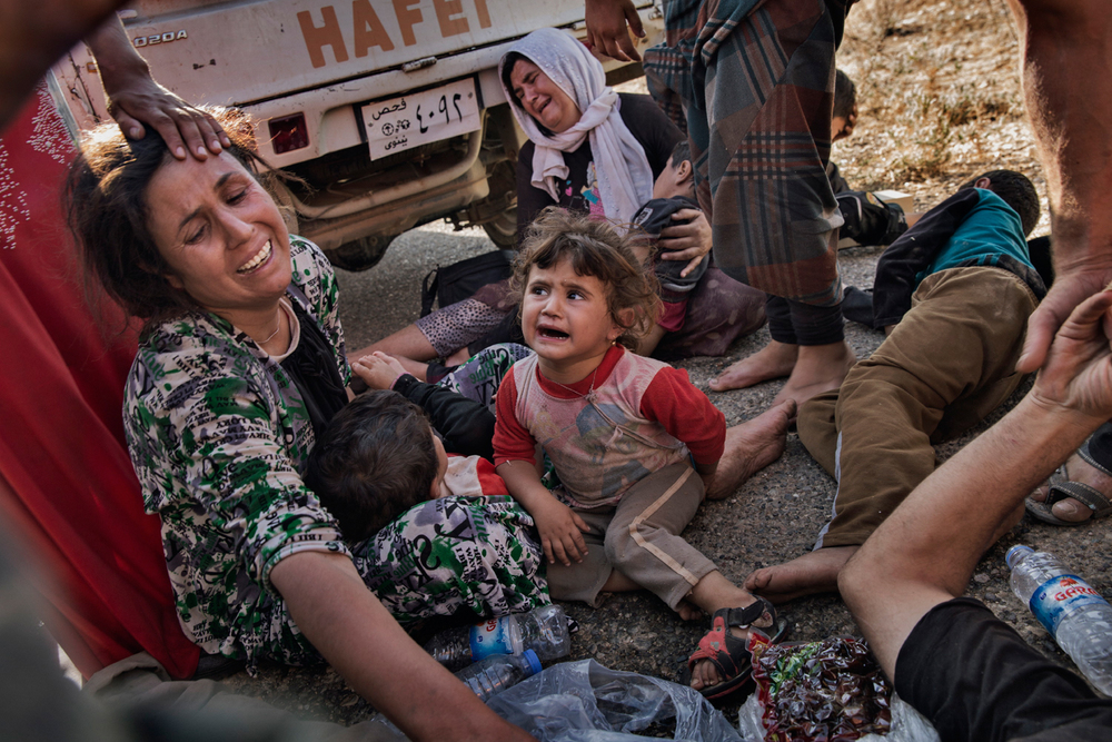 Displaced Iraqi Yazidis scream after surviving a helicopter crash in the mountains of Sinjar, Nineveh Province, Iraq on Aug. 12, 2014. After delivery aid and picking up a number of IDPs, the helicopter crashed wounding many and killing the pilot. Photo by Adam Ferguson for The New York Times