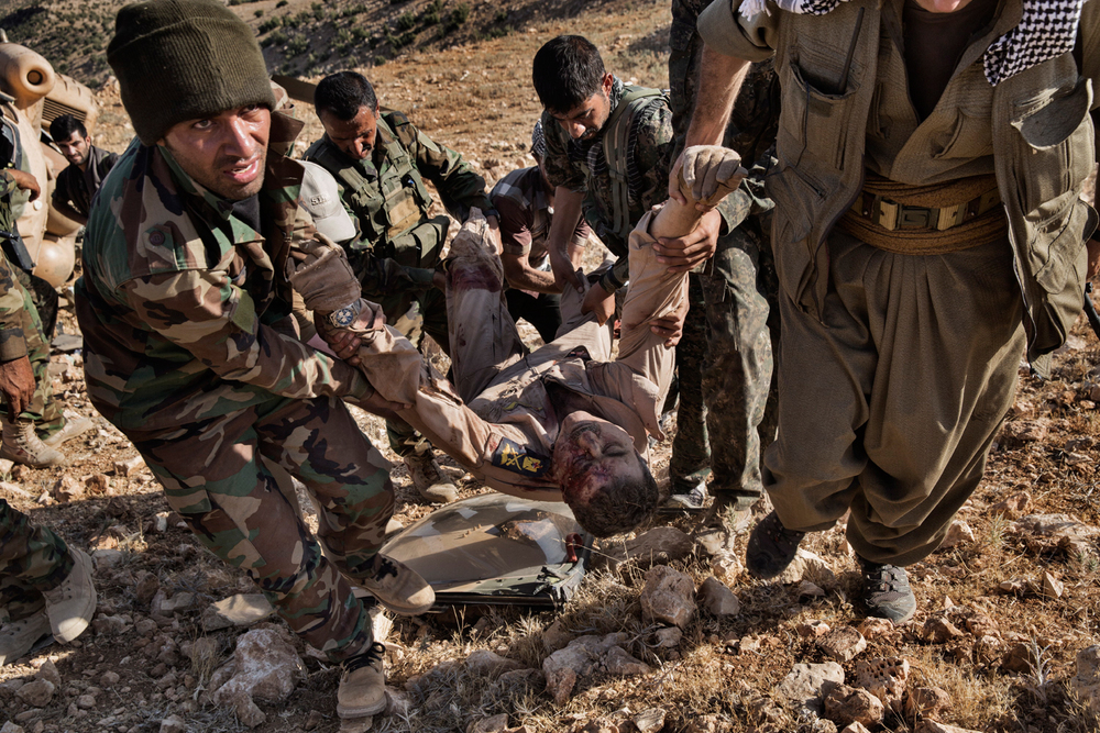 Kurdish peshmerga forces carry the body of the pilot of a helicopter that crashed in the mountains of Sinjar, Nineveh Province, Iraq on Aug. 12, 2014. After delivery aid and picking up a number of IDPs, the helicopter crashed wounding many and killing the pilot. Photo by Adam Ferguson for The New York Times