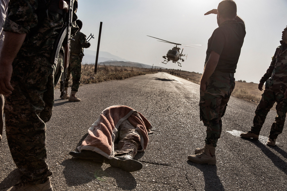 The body of a helicopter pilot that was killed when his helicopter crashed while rescuing Yazidis from the mountain of Sinjar, rests on a road in the mountains of Sinjar, Nineveh Province, Iraq on Aug. 12, 2014. After delivery aid and picking up a number of IDPs, the helicopter crashed wounding many and killing the pilot. Photo by Adam Ferguson for The New York Times