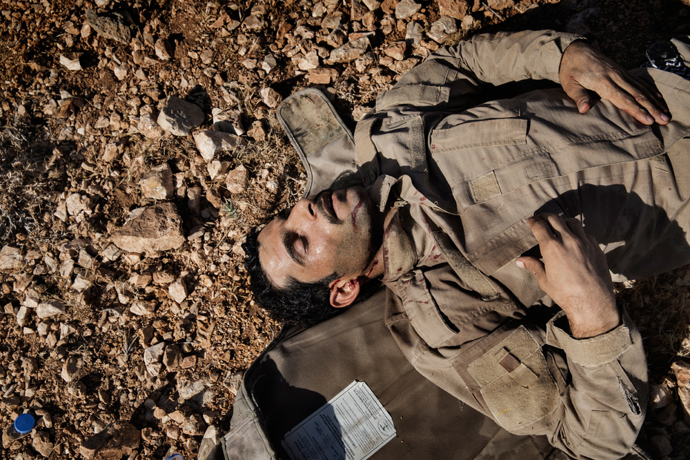 A wounded Iraqi military person lies on the ground after the helicopter he was manning crashed in the mountains of Sinjar, Nineveh Province, Iraq on Aug. 12, 2014. After delivery aid and picking up a number of IDPs, the helicopter crashed wounding many and killing the pilot. Photo by Adam Ferguson for The New York Times
