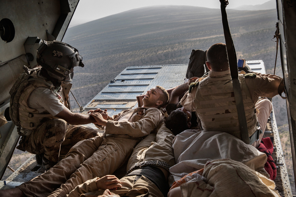 Kurdish peshmerga forces, displaced Yazidi and Iraqi military personal that were wounded in a helicopter crash, fly on a rescue helicopter back to medical facilities in Kurdistan, over the mountains of Sinjar, Nineveh Province, Iraq on Aug. 12, 2014. After delivery aid and picking up a number of IDPs, an Iraqi military helicopter crashed wounding many and killing the pilot. Photo by Adam Ferguson for The New York Times