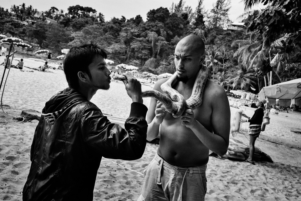 Mourad Kateb, age 23, from a Banlieue in Paris, France, plays with a python on a beach in Phuket, Thailand on Feb. 18, 2015. Kateb is Muslim and is travelling with his younger cousin in Thailand.Photo by Adam Ferguson