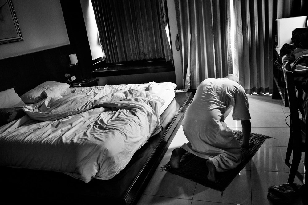 Mourad Kateb, age 23, from a Banlieue in Paris, France, prays in his hotel room in Patong, Phuket, Thailand on Feb. 18, 2015. Kateb is Muslim and is travelling with his younger cousin in Thailand.Photo by Adam Ferguson