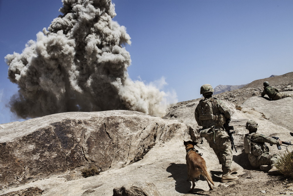 Military Working Dog handler SSG Jonathan Bourgeois and his MWD Oopey, a Belgian Malinois patrol explosives dog, take cover during the controlled detonation of a road during an operation in Mya Neshin, Kandahar, Afghanistan. Adam Ferguson for National Geographic
