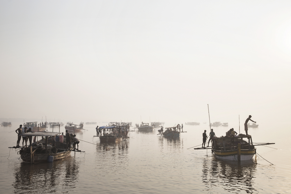 Sand mining boats work illegally on the Thane River near Nagla Bunder Village in Maharashtra, India.