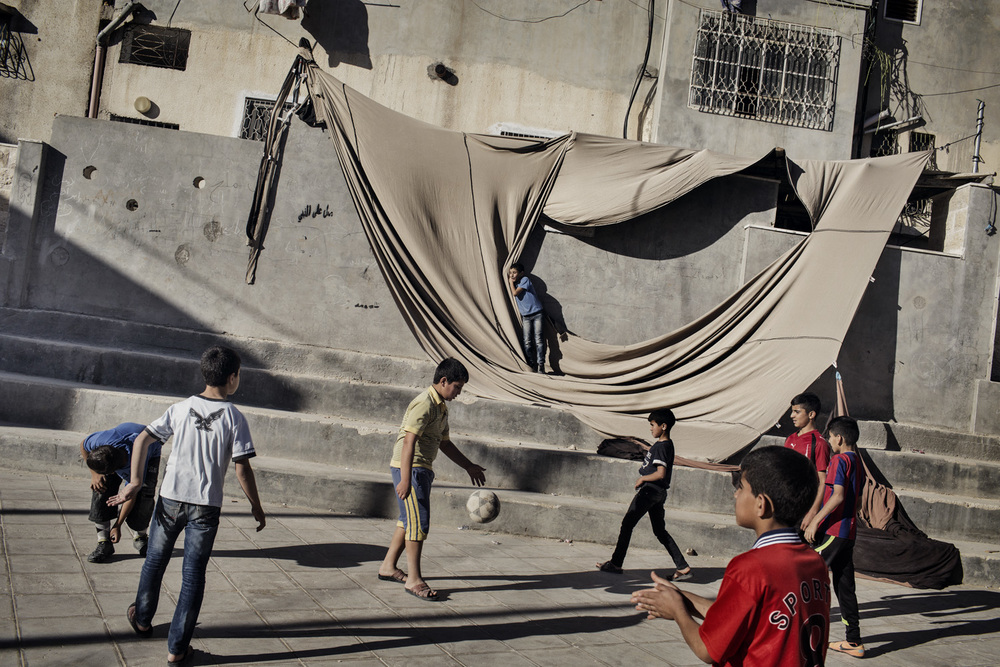 'WEST BANK' for The New York Times:  Palestinian children play soccer in a public square at the Fawwar refugee camp in Hebron, West Bank, Palestinian Territories.