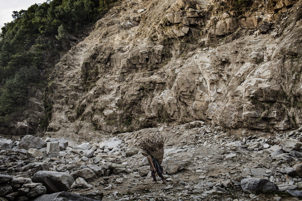 A local villager traverses a landslide between Bung and Cheskam villagers near Bung Village, Solukhumbu District, Nepal. The April 2015 earthquakes caused a landslide that destroyed the footbridge between Bung and Cheskam villages, making it treacherous for locals to commute and trade.