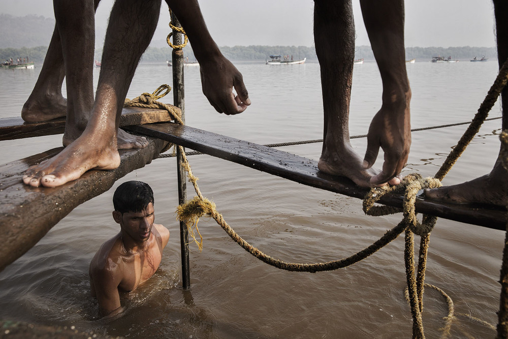 Sand mining boats work illegally on the Thane River near Nagla Bunder Village in Maharashtra, India, 2015. Indian workers dive to the bottom of the river with a metal bucket to scoop sand that is hauled to the water surface by the boat crew. As construction and industry drive a demand for sand, illegal sand mining is stripping riverbeds and beaches of sand with severe environmental consequences. The unregulated sand mining industry employs thousands of workers who depend on the mining for their livelihood and is controlled by local powerbrokers. Photo by Adam Ferguson for WIRED