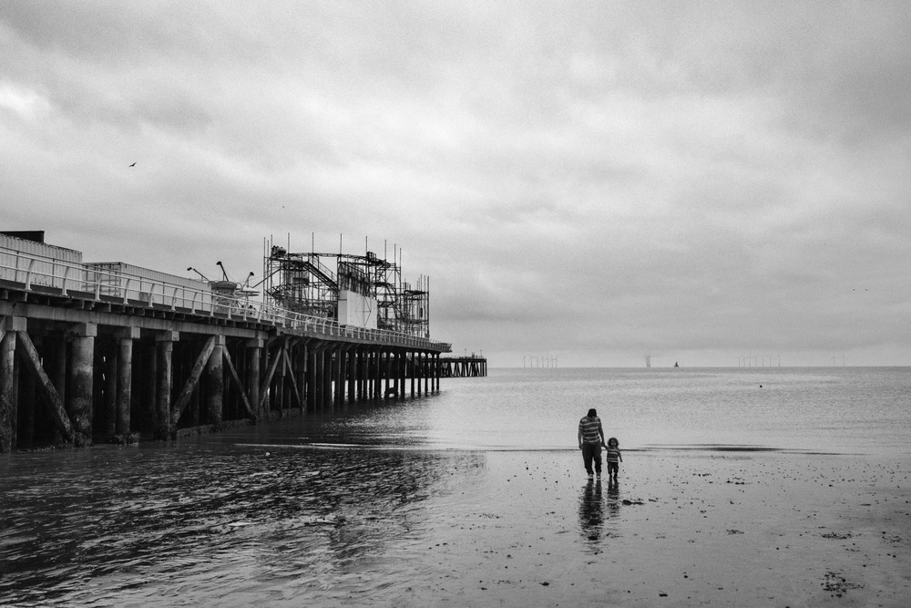 People walk on the beach in Clacton-on-Sea in Essex, England, United Kingdom.