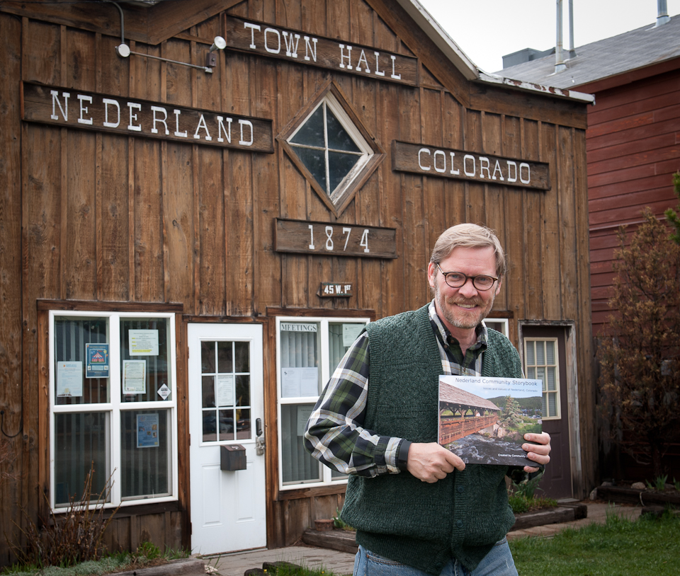 Nederland, Colorado, Mayor Joe Gierlach holding a copy of the Nederland Community Storybook