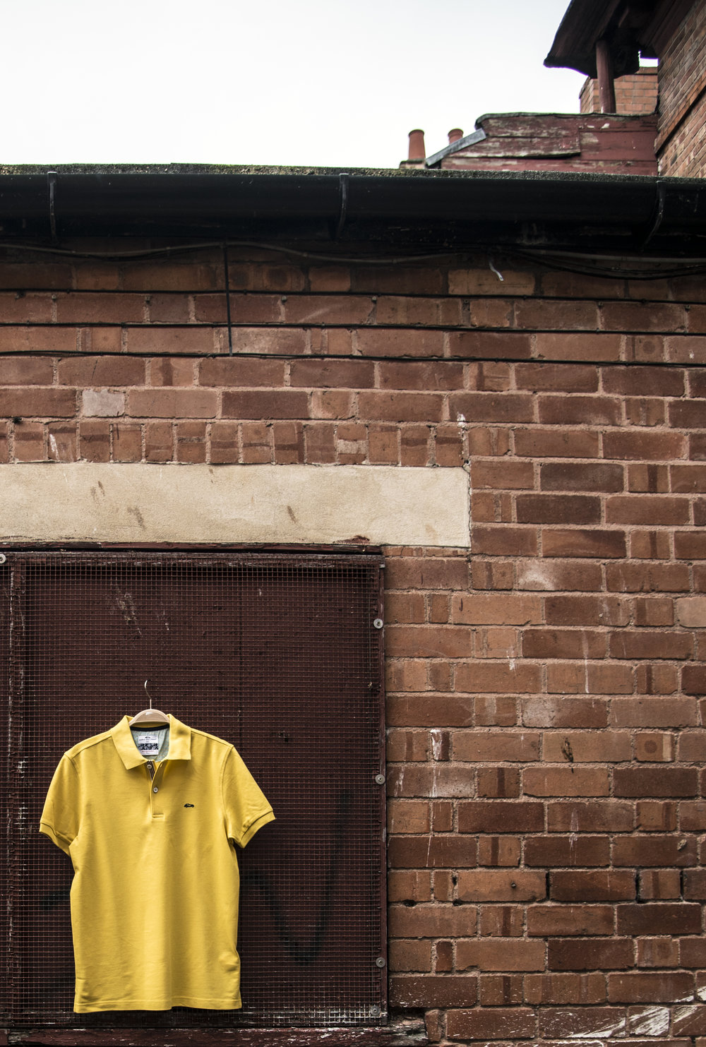 Yellow polo shirt hanging off wall in Hereford.jpg