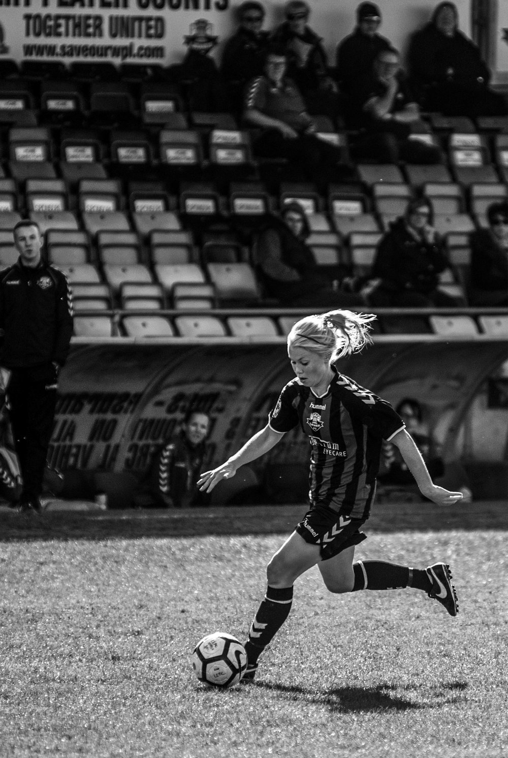 Woman footballer dribbling with ball backlit.jpg