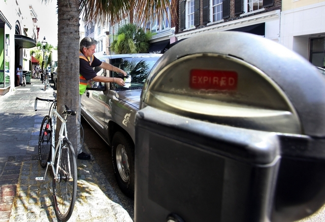 Bobby Johnson leaves a ticket on a car on King Street in downtown Charleston, S.C.  By Brad Nettles / The Post and Courier