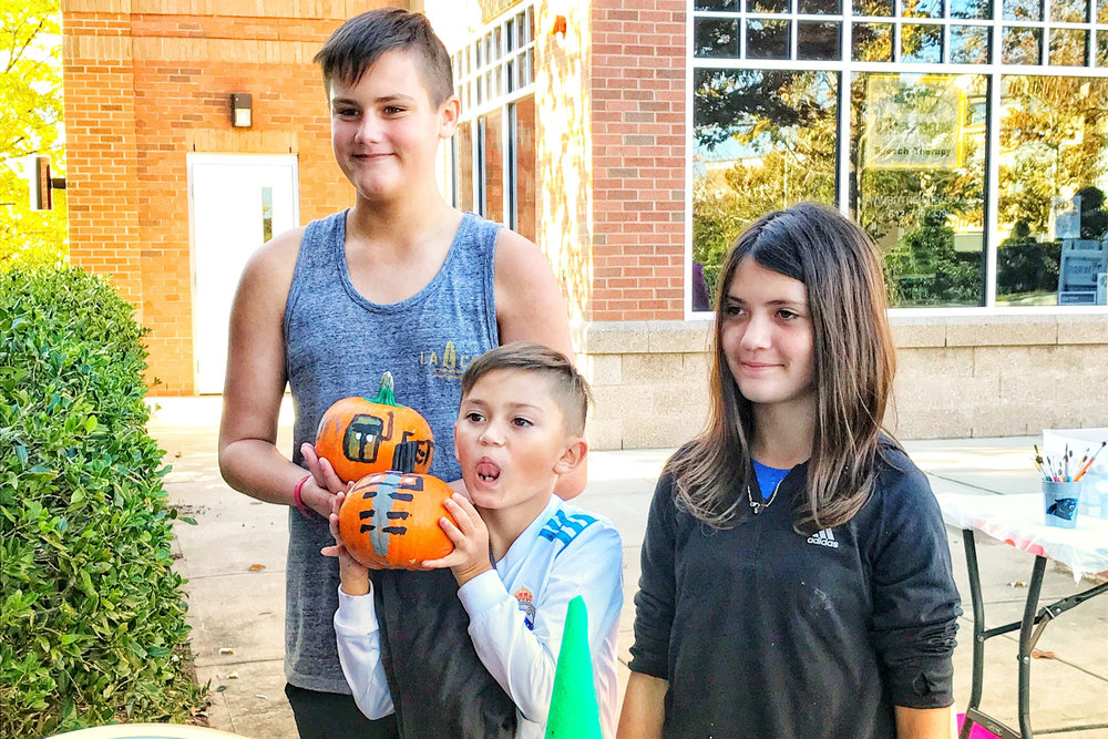 3 kids with painted pumpkins.jpg