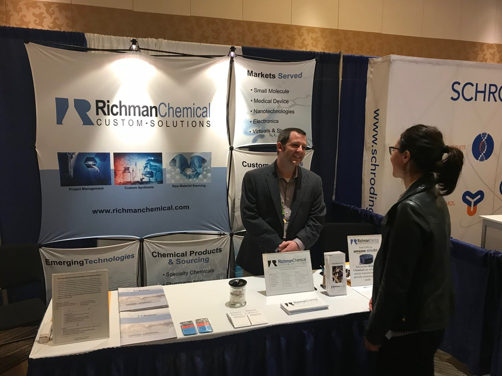 Richman Chemical Project Manager, Custom Manufacturing, Scott Heston, speaking with an attendee of the CHI's Drug Discovery Chemistry expo in San Diego, CA.