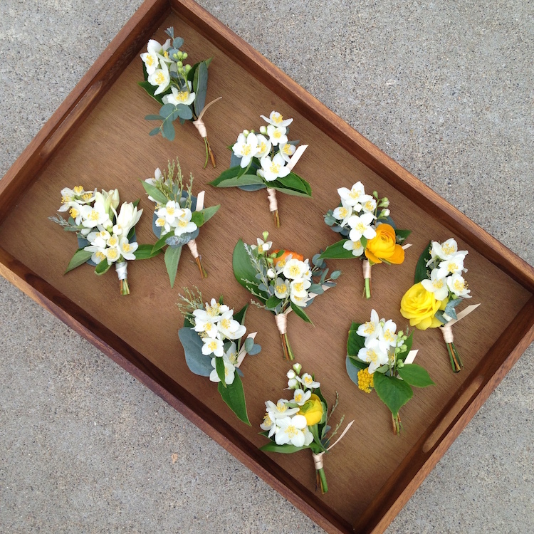 Orange blossom & ranunculus boutonnieres by San Diego wedding florist, Compass Floral.