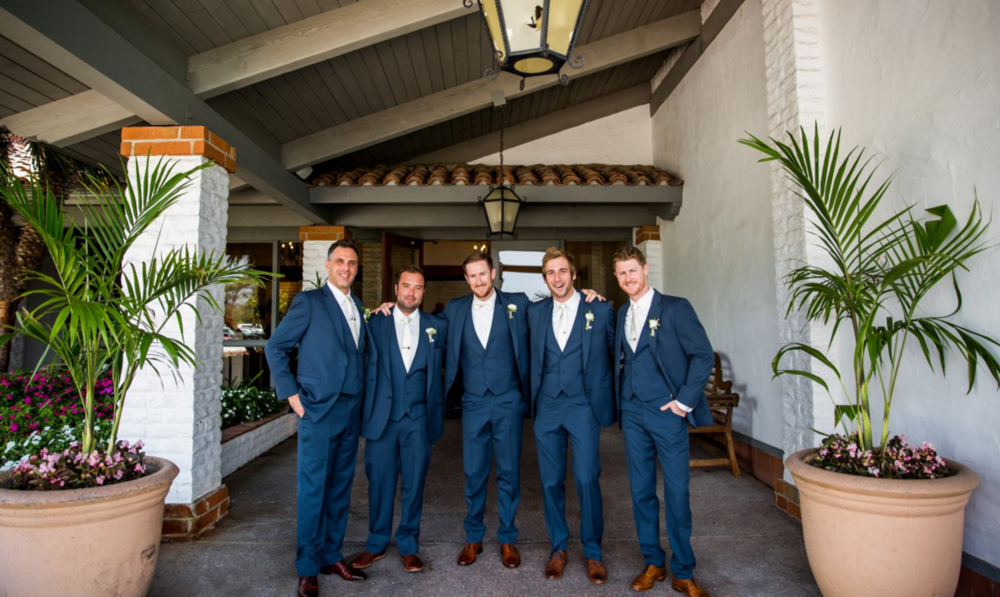 Groomsmen in blue suits. White ranunculus boutonnieres by San Diego wedding florist, Compass Floral.