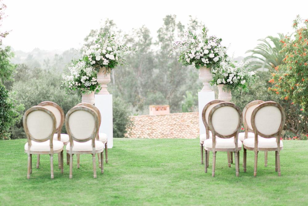 Elegant white pedestal wedding ceremony by Compass Floral | Rancho Valencia, Rancho Santa Fe.