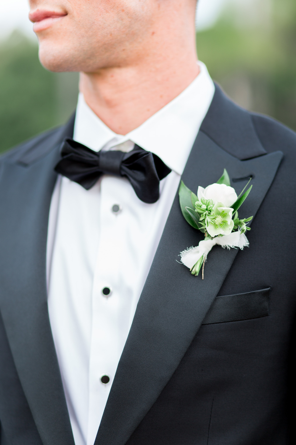 White ranunculus and hellebore boutonniere by Compass Floral | Rancho Valencia, Rancho Santa Fe.