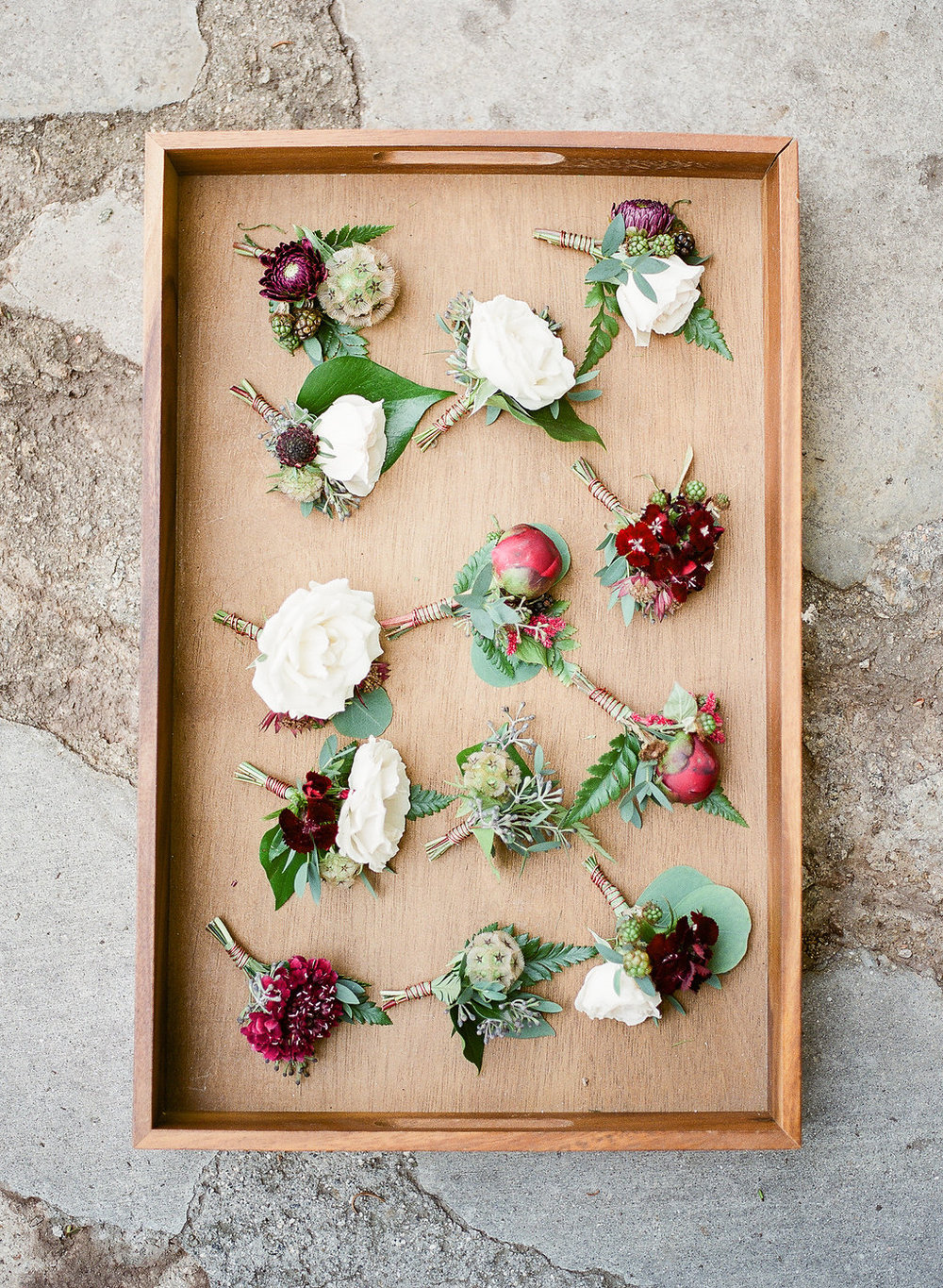Mismatched burgundy and white boutonnieres by Compass Floral | Fallbrook Treehouse, Fallbrook