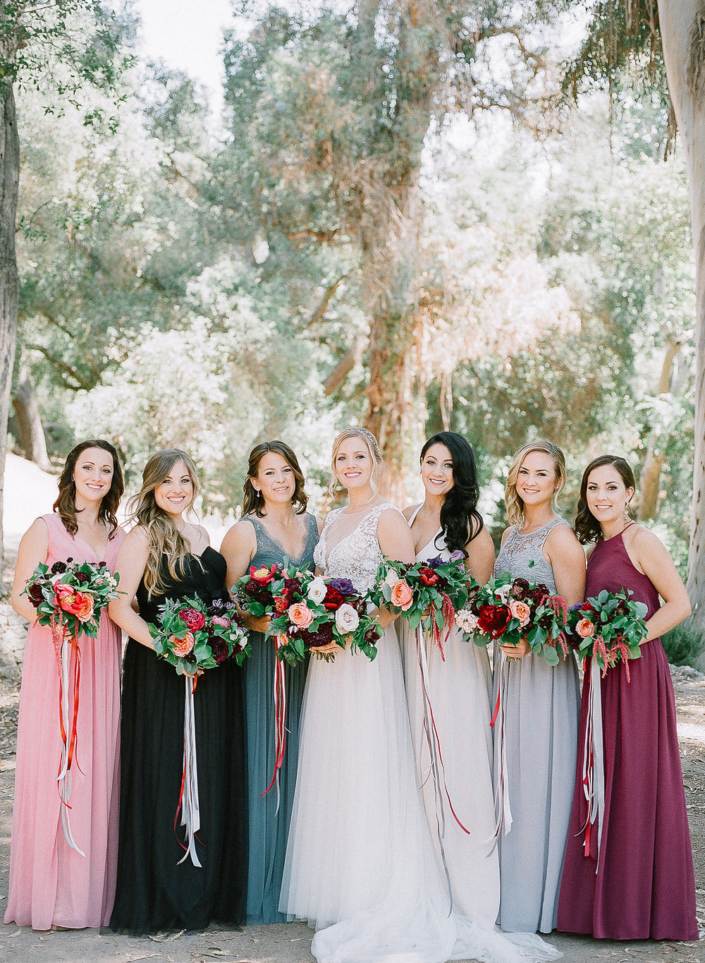 Mismatched bridesmaid dresses with jewel tone bouquets and trailing ribbons by Compass Floral | Fallbrook Treehouse, Fallbrook