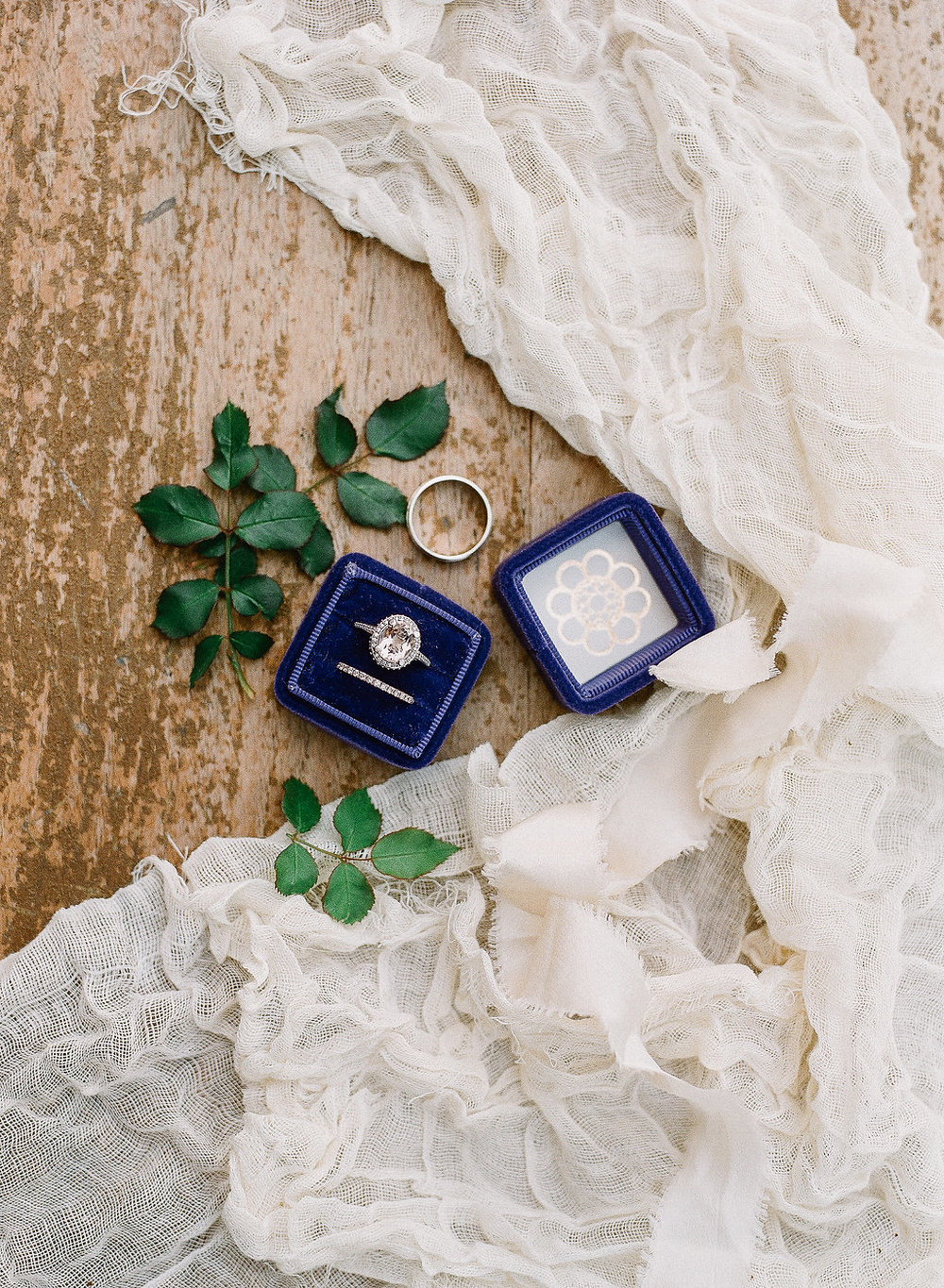 Blue ring box styled with elegant fabric and greens | Photographed by Allie Lindsey