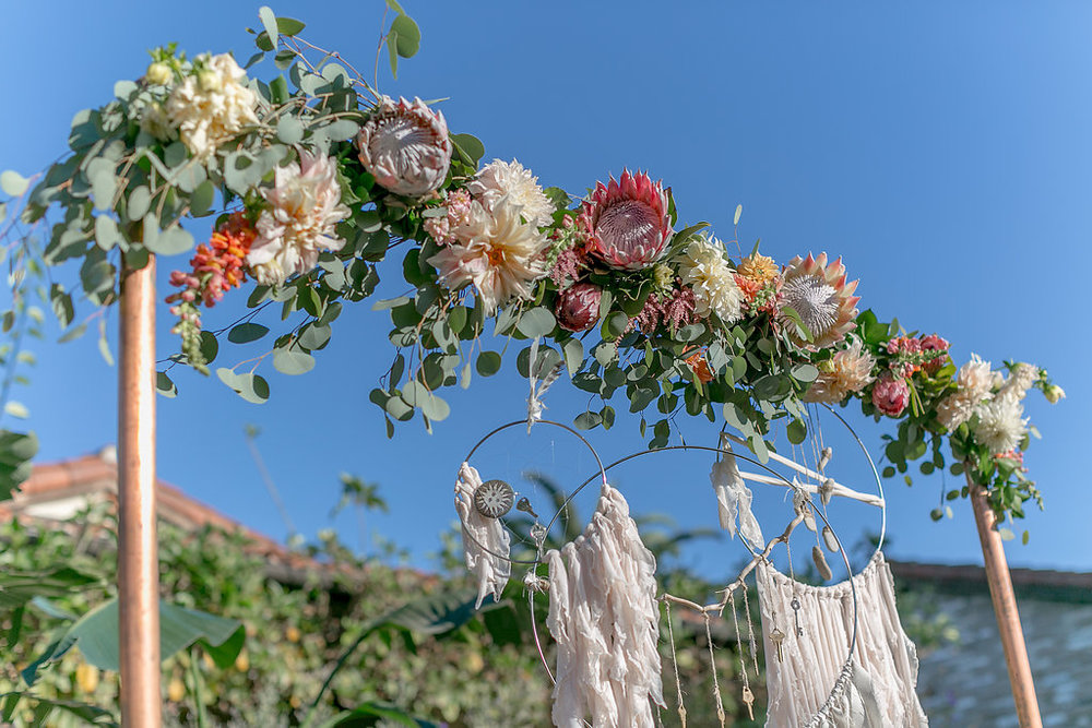 Desert bohemian wedding ceremony with copper arch and floral garland by Compass Floral | Estancia Hotel & Spa, La Jolla.