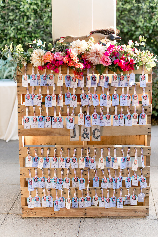 Bohemian wedding escort card display with floral garland by Compass Floral | Estancia Hotel & Spa, La Jolla.