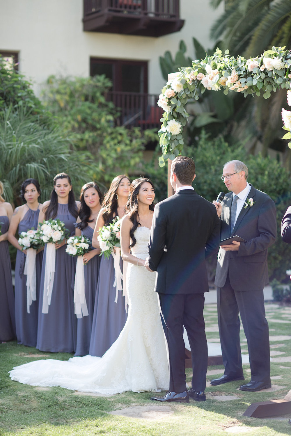 Wood arch with garland wedding ceremony at Estancia Hotel & Spa, La Jolla by Compass Floral.