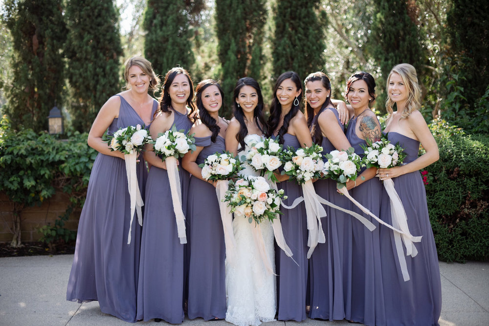 Purple bridesmaids with neutral bouquets by Compass Floral | Estancia Hotel & Spa, La Jolla
