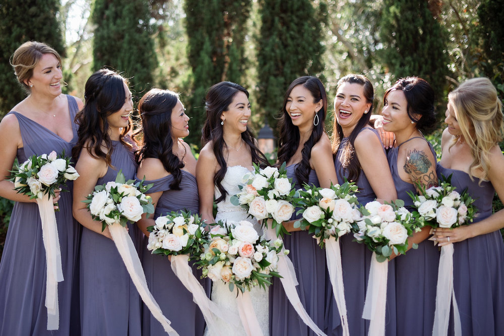 Purple bridesmaids with neutral bouquets Arch with garland wedding ceremony at Estancia Hotel & Spa, La Jolla by Compass Floral.