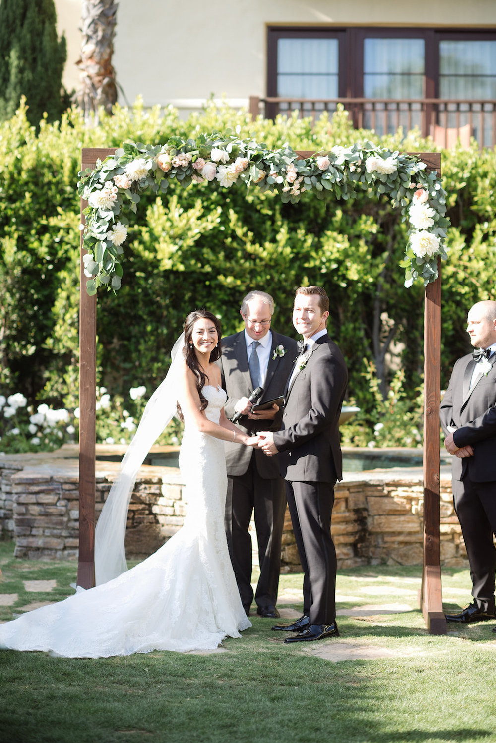 Wood arch with floral garland by Compass Floral | Estancia Hotel & Spa, La Jolla