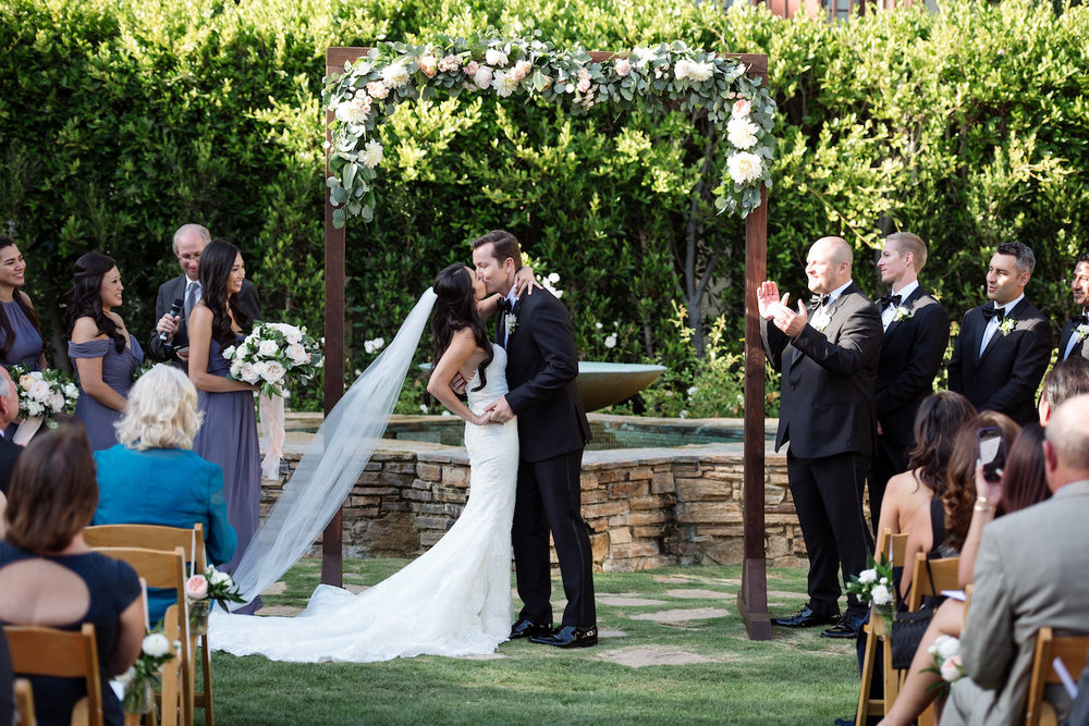 Wood arch with floral garland wedding ceremony by Compass Floral | Estancia Hotel & Spa, La Jolla.