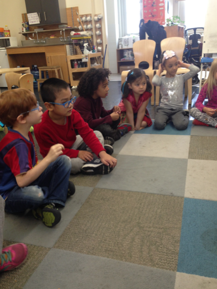 Kindergarteners getting in a circle sitting criss-cross to begin Morning Meeting